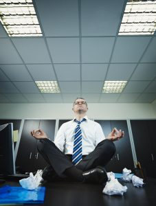 stressed businessman sitting on desk in lotus position. Vertical shape, full length, Copy space